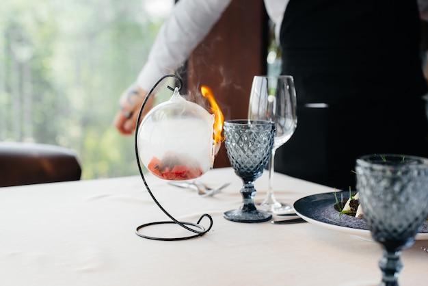 Ein exquisiter salat aus meeresfrüchten, thunfisch und schwarzem kaviar in einem schönen brennen mit feuer, das auf dem tisch im restaurant serviert wird. exquisite köstlichkeiten der haute cuisine hautnah.