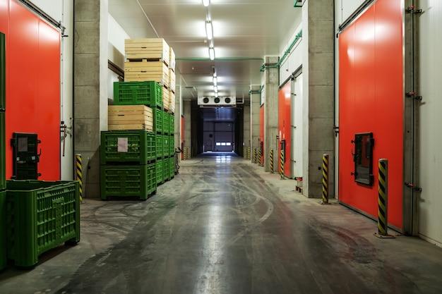 Ein fabriklager ohne menschen darin. leerer lagerraum mit vielen paletten, die im werk ordentlich gestapelt sind. die dunkle atmosphäre eines geschlossenen lagers ohne menschen. vertrieb und logistik