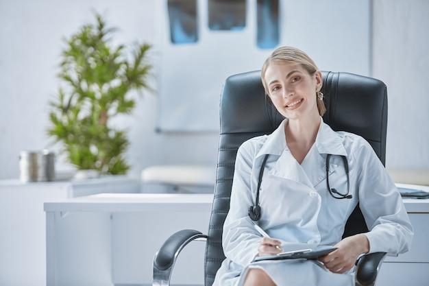 Ein facharzt sitzt auf einem bürostuhl mit einem stethoskop um den hals