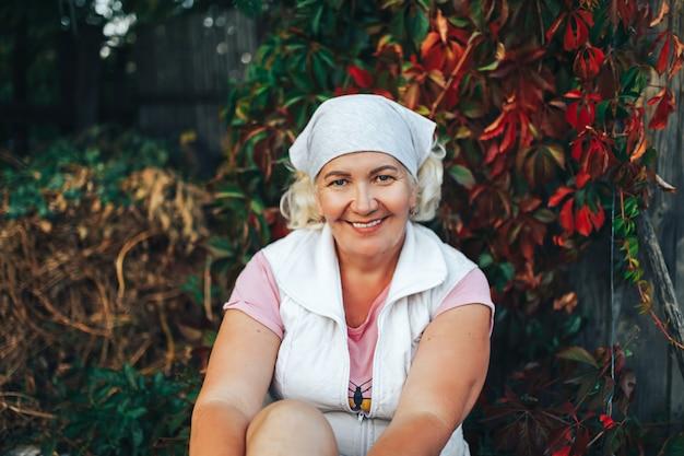Ein fälliger lächelnder weiblicher gärtner oder eine frau, die im garten mit schal auf ihrem kopf sitzen