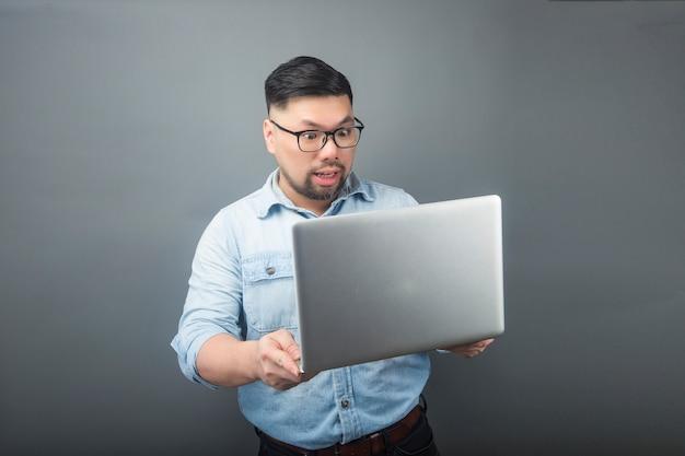 Ein fälliger mann, der einen computer und einen kaffee anhält