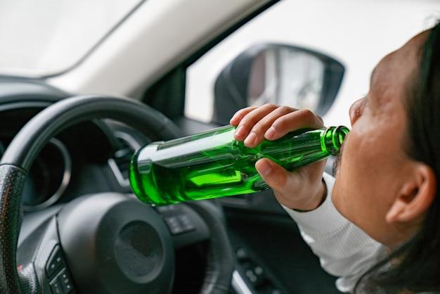 Ein fahrer, der alkoholische flasche beim fahren hält