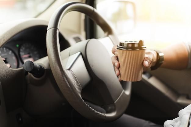 Ein fahrer, der kaffee im auto trinkt.