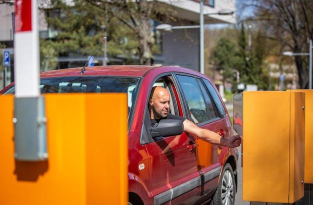 Ein fahrer des autos, der das parken mit einer kreditkarte bezahlt, zahlungsvorgang