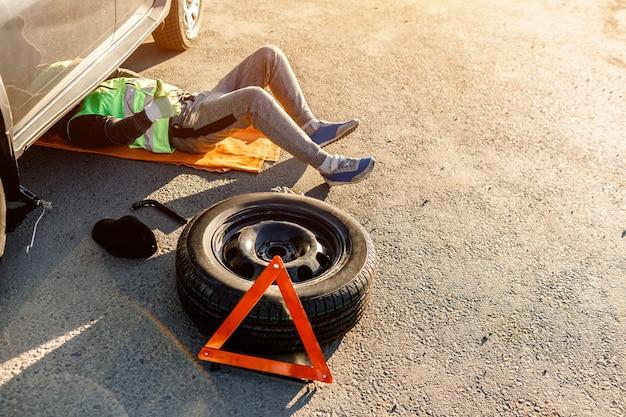 Ein fahrer oder arbeiter repariert ein kaputtes auto am straßenrand. von oben betrachten. mann ist unter dem auto