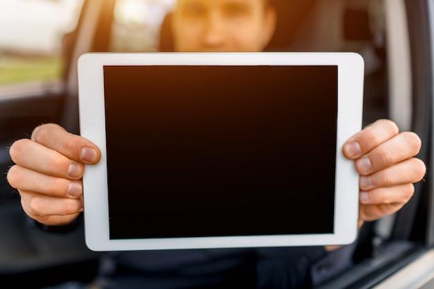 Ein fahrer zeigt einen tablet-pc-bildschirm in nahaufnahme in der kamera. leerer platz für ihren text oder ihre grafiken.