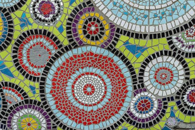 Ein farbenfrohes mosaik mit kaleidoskopkreisen aus zerbrochenen keramikfliesen.