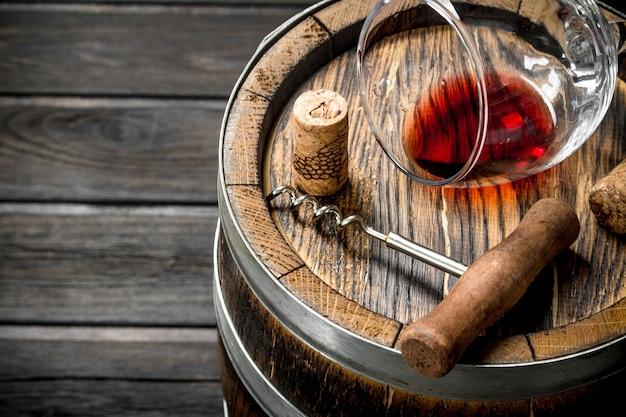 Ein fass rotwein und ein korkenzieher auf einem holztisch.