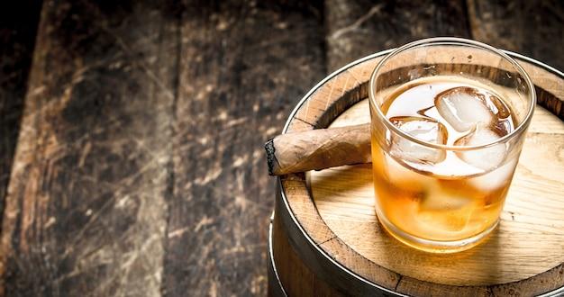 Ein fass scotch whisky mit glas und einer zigarre
