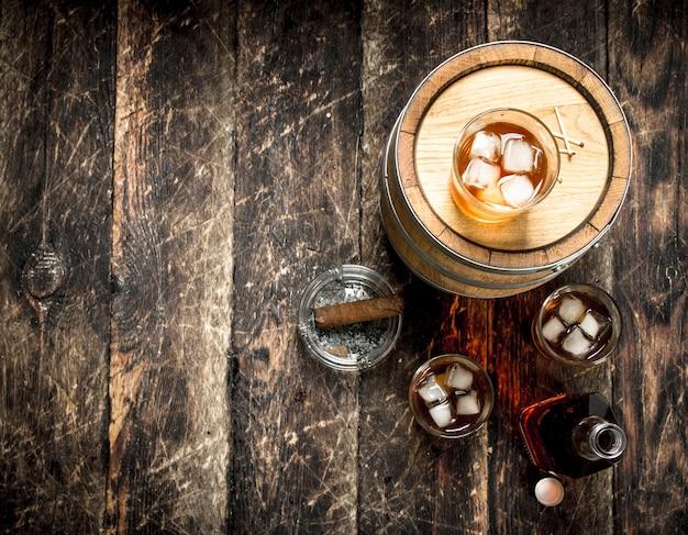 Ein fass scotch whisky mit glas und einer zigarre.