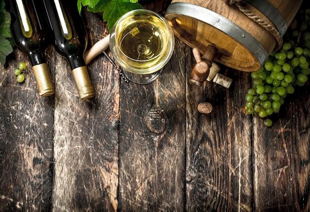 Ein fass weißwein mit zweigen grüner trauben auf holztisch.