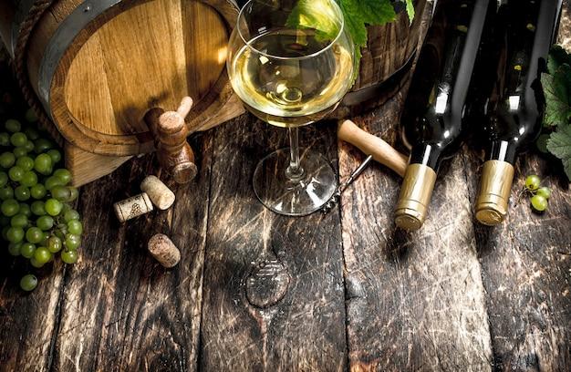 Ein fass weißwein mit zweigen grüner trauben.