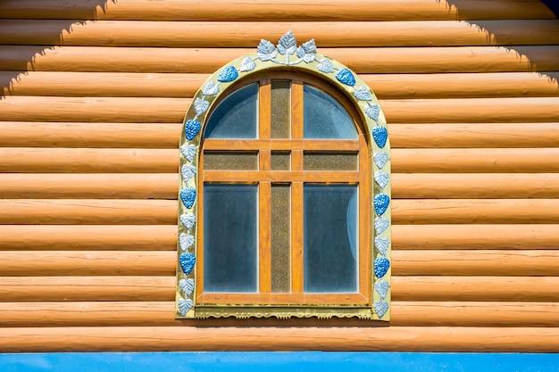 Ein fenster mit elementen des dekors der hölzernen orthodoxen kirche an einem sonnigen tag