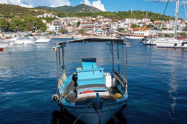 Ein festgemachtes boot aus holz im ägäischen seehafen, gebäude in neos marmaras, griechenland