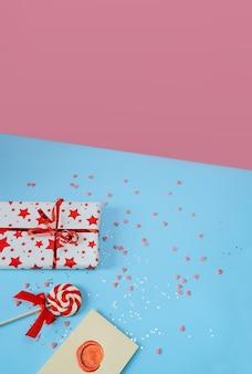 Ein festlicher lutscher, ein brief und eine geschenkbox liegen auf einem blauen hintergrund in einer isometrischen projektion. konzept der liebe und feier des valentinstags.
