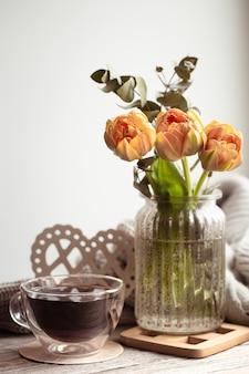 Ein festliches stillleben mit einem blumenarrangement in einer vase und einer tasse tee und gemütlichen dingen.