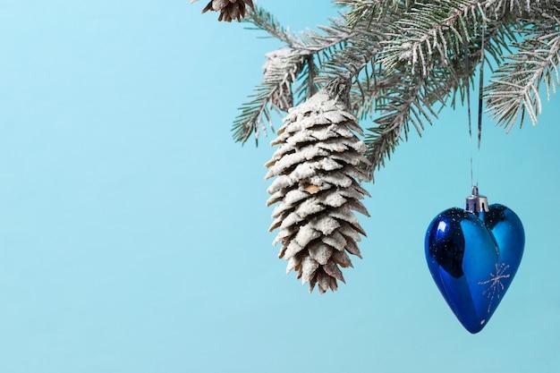 Ein fichtenzweig, verziert mit einem herzförmigen spielzeug. vorbereitung auf weihnachten
