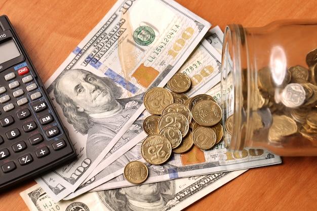 Ein finanzielles stillleben mit einem glas sterling-münzen auf sterling-banknoten, taschenrechner-dollars auf dem tisch