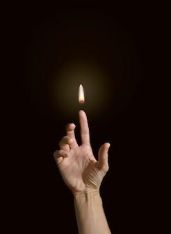 Ein finger, der eine flamme hält