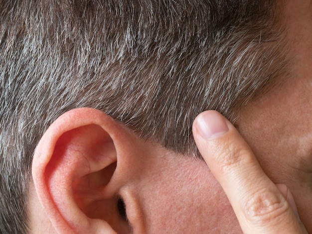 Ein finger zeigte auf das graue haar auf seinem kopf.