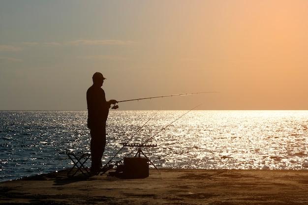Ein fischer fischt mit einer angel am meeresufer, gegenüber der sonne. foto in hoher qualität