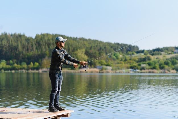 Ein fischer mit einer angelrute am flussufer