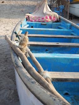 Ein fischerboot, innen blau lackiert, steht an einem sandstrand, nahaufnahme.
