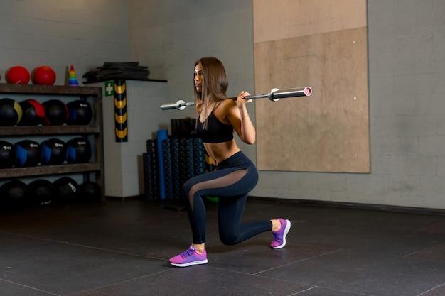 Ein fitness-trainer für junge mädchen in leuchtend rosa turnschuhen macht eine trainingshocke mit einer langhantel im fitnessstudio.