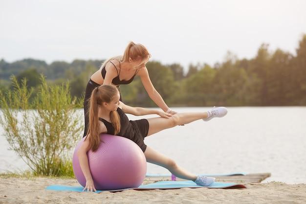 Ein fitnesstrainer leitet einen kurs für ein mädchen auf einem gymnastikball