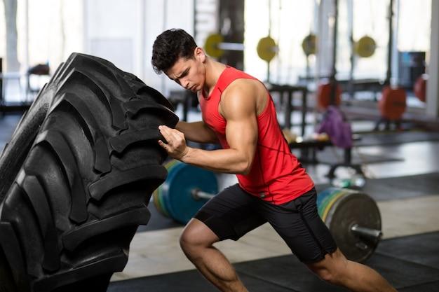 Ein fitter, athletischer junger mann in der sportbekleidung, die kraftübung mit großem rad im fitnessstudio macht.
