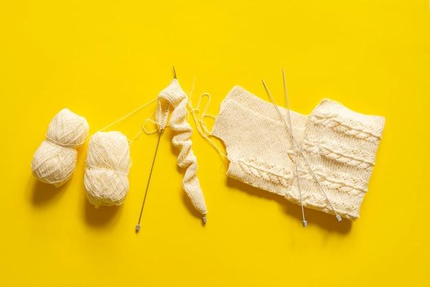 Ein flach liegender strick liefert ausrüstung, handgemachte wollkleidung