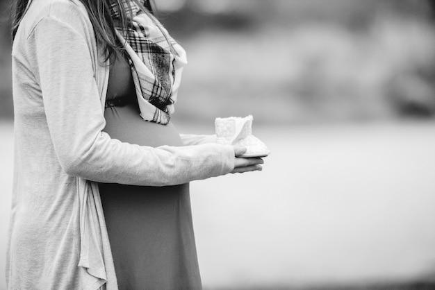 Ein flacher fokusschuss einer schwangeren frau, die neugeborene schuhe hält