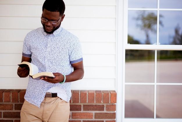 Ein flacher fokusschuss eines afroamerikanischen mannes, der die bibel liest