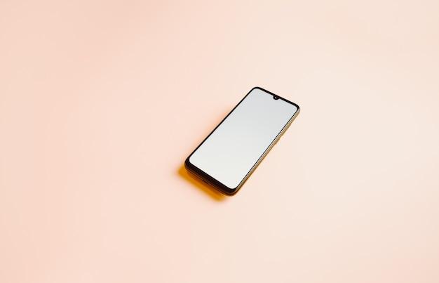 Ein flacher rosa hintergrund mit einem mobiltelefon mit einem weißen bildschirm und kopierraum zum beschreiben