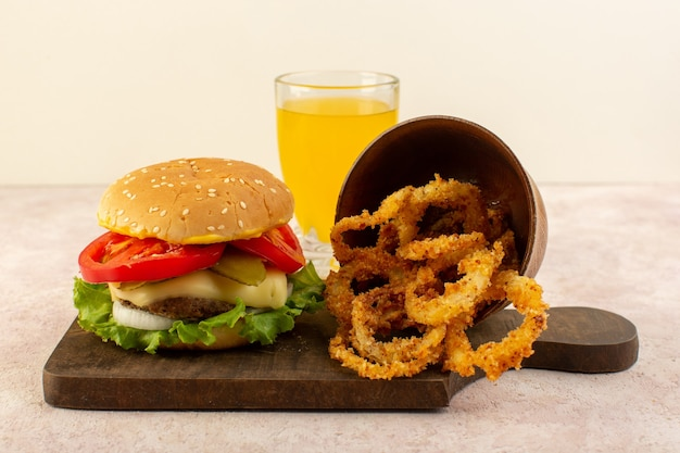 Ein fleischburger von vorne mit käsesaft und grünem salat und hühnerflügeln auf dem holztisch