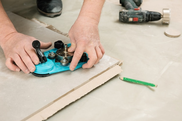 Ein fliesenleger verwendet einen messschieber mit saugnapf, um löcher in die keramikfliese aus nächster nähe zu bohren