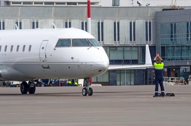 Ein fluglotsen-bodenpersonal, das ein flugzeug auf einer landebahn eines flughafens führt.