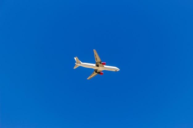 Ein flugzeug fliegt in den blauen himmel ohne weiße wolken