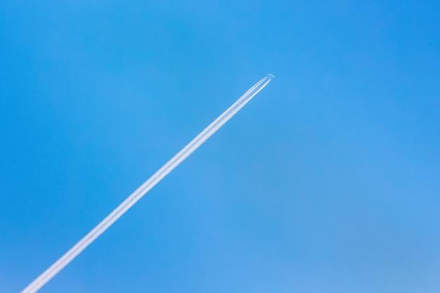 Ein flugzeug und eine spur von einem flugzeug in einem blauen himmel