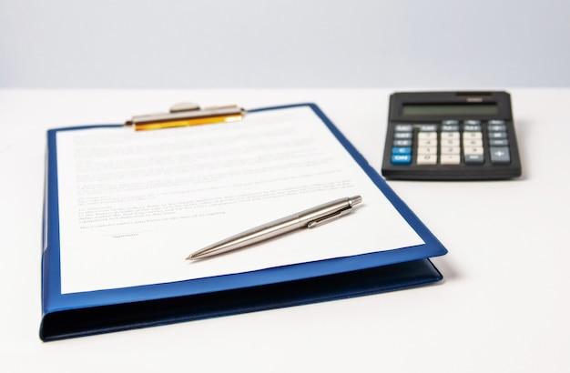 Ein formular zum signieren eines blauen ordners mit einem clip mit einem stift und einem taschenrechner auf hellem hintergrund.