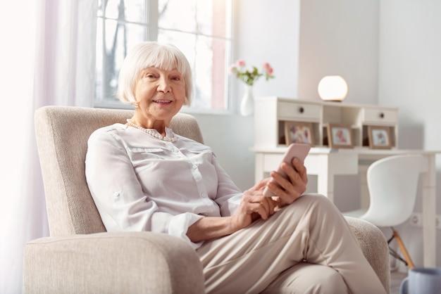 Ein fortgeschrittener benutzer. fröhliche ältere frau, die in einem sessel sitzt und lächelt, während sie auf ihrem telefon im internet surft
