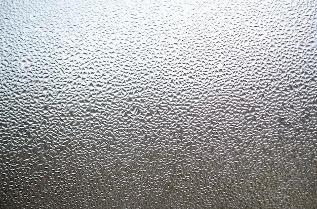 Ein foto der glasoberfläche des fensters, bedeckt mit einer vielzahl von tröpfchen unterschiedlicher größe. hintergrundbeschaffenheit einer dichten kondensatschicht auf glas