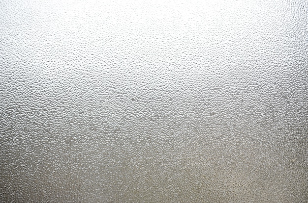 Ein foto der glasoberfläche des fensters, bedeckt mit einer vielzahl von tröpfchen unterschiedlicher größe. hintergrundbeschaffenheit einer dichten schicht kondensat auf glas