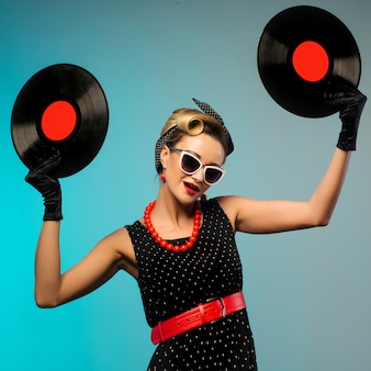 Ein foto des glamourösen pin-up-mädchens, das vinyl-lp in der hand hält