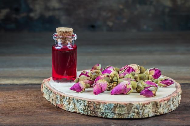 Ein foto des rosenöls in der kleinen glasflasche auf hölzerner platte