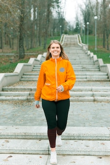 Ein foto einer glücklichen jungen sportlerin, die am morgen mit dem lächeln auf ihrem gesicht im park läuft