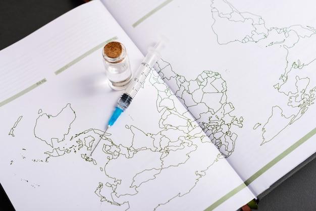 Ein foto einer karte und eines impfstoffs darüber zeigt, dass der impfstoff weltweit gültig ist