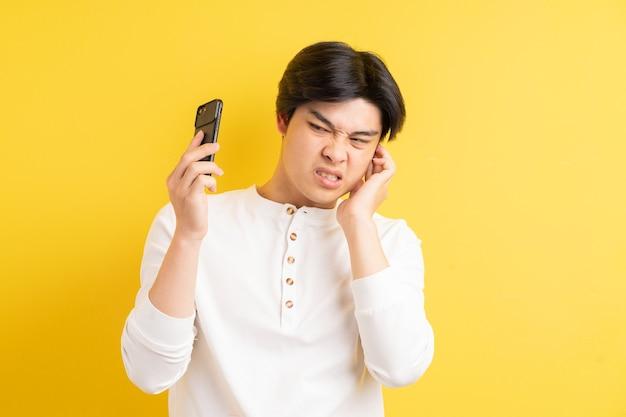Ein foto eines asiatischen mannes, der beim telefonieren ins ohr geschrien wird