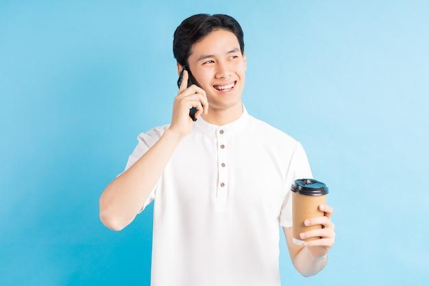 Ein foto eines gutaussehenden asiatischen mannes, der anruft und eine tasse kaffee in seiner hand hält