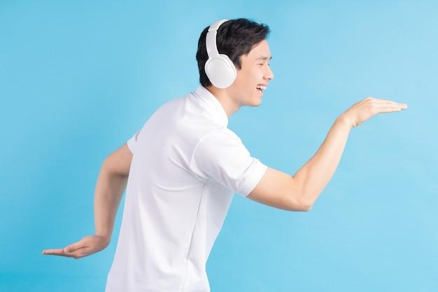 Ein foto eines gutaussehenden asiatischen mannes, der musik hört und dazu tanzt